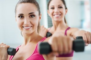 Cheerful young women exercising at the gym and weightlifting using dumbbells, they are smiling at camera